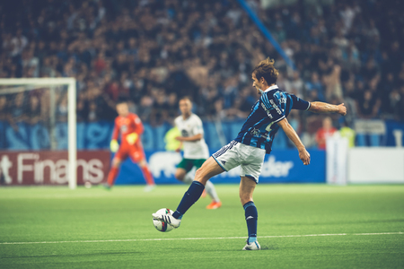 rivals: STOCKHOLM, SWEDEN - AUG 24, 2015: Jesper Karlstrom (DIF) kicking the ball at the soccer game between the rivals Djurgarden and Hammarby at Tele2 arena.