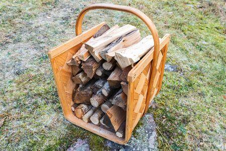 log basket: Firewood basket outside on frosty grass during winter. Sweden