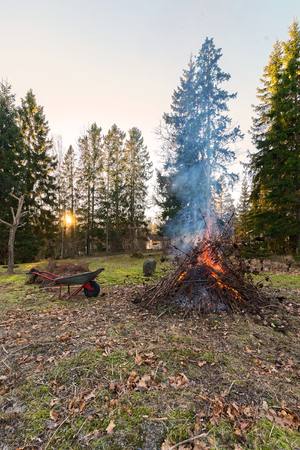 Fire during cleanup of garden with sun setting and an old wheelbarrow. Sweden Stock Photo