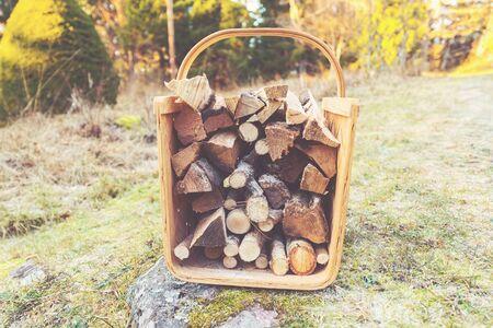 log basket: Firewood basket outside on frosty grass during winter. Filter applied