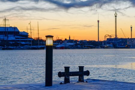 very cold: Light on a pole with Stockholm in background during a very cold morning before sunrise. Stock Photo