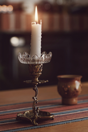 Candellight on a table in a cozy enviroment. Filter applied