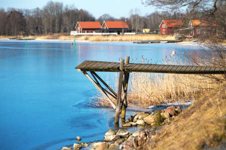 horisontal: Wooden jetty during early spring with thin ice on water.