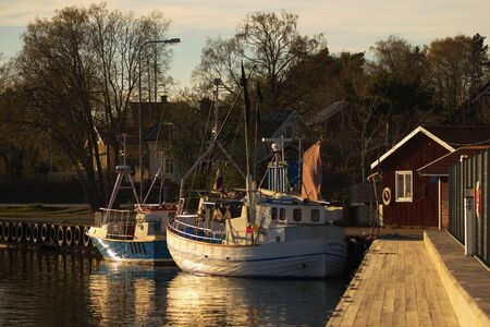NORRTALJE, SWEDEN - MAY 5, 2016: Warm light over the fishing harbour at Grisslehamn during late hours. Editorial