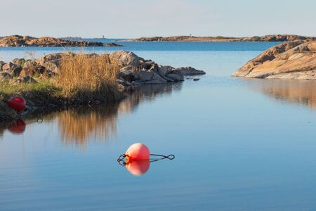 floaters: View over a small bay during late afternoon with red floaters. Grisslehamn, Sweden