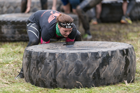 tough: STOCKHOLM, SWEDEN - MAY 14, 2016 Woman flipping tires at Tough Viking obstacle course around Stockholm.