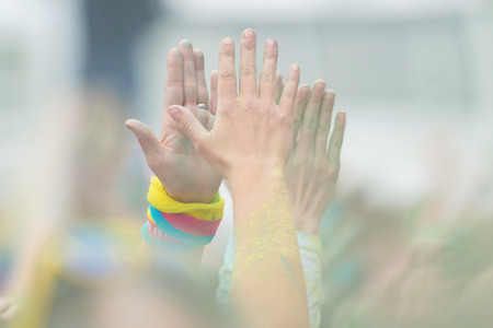stretch out: STOCKHOLM, SWEDEN - MAY 22, 2016: Clapping hands stretch out to the sky at Color Run Tropicolor world tour in Stockholm.