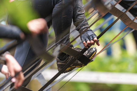 STOCKHOLM, SWEDEN - MAY 14, 2016 Closeup of feet climbing the A- frame at Tough Viking obstacle course around Stockholm Stadion. Sajtókép