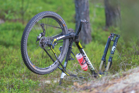 ongoing: TULLINGE, SWEDEN - JUNE 12, 2016: Ongoing repairing of  a puncture in the forests at Lida loop during summer. One of swedens biggest mountainbike races.