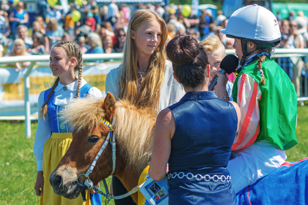 recieving: STOCKHOLM, SWEDEN - JUNE 6, 2016: Winner at the pony race recieving prize at Nationaldags Galoppen at Gardet with the crowd behind.