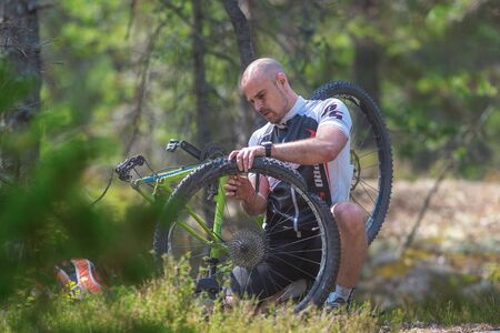 TULLINGE, SWEDEN - JUNE 12, 2016: MTB cyclists repairing a puncture in the forests at Lida loop during summer. One of swedens biggest mountainbike races. Sajtókép