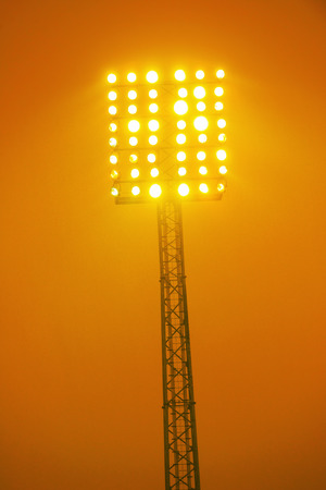 floodlights: Floodlights on a high tower in yellow color, orange background and high contrast Stock Photo