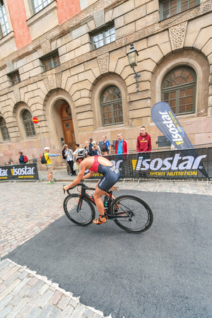 ber: STOCKHOLM, SWEDEN - JULY 02, 2016: Flora Duffy (BER) cycling thru the old town at the Women ITU Triathlon event in Stockholm.