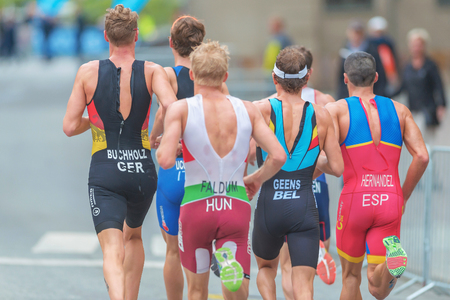 elite: STOCKHOLM, SWEDEN - JULY 02, 2016: Back of a group of elite pro triathletes running at the Mens ITU Triathlon event in Stockholm.