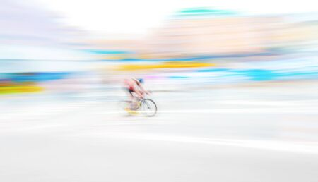 extreme angle: Cyclist in extreme motion blur capture in bright and vivid colors on a city road. Wide angle shot. Editorial