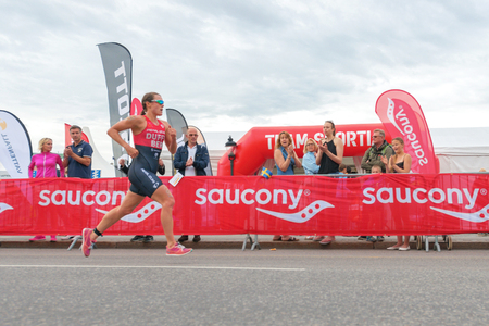ber: STOCKHOLM, SWEDEN - JULY 02, 2016: Leader Flora Duffy (BER) running in wide angle view at the Women ITU Triathlon event in Stockholm.