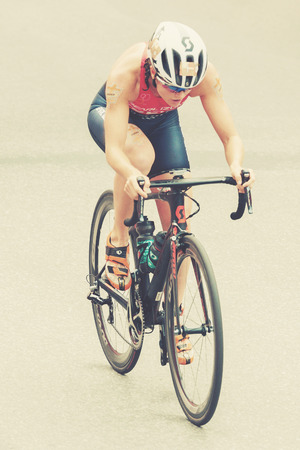 ber: STOCKHOLM, SWEDEN - JULY 02, 2016: Leader Flora Duffy (BER) from above cycling at the Women ITU Triathlon event in Stockholm. Filtered