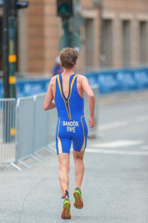 gabriel: STOCKHOLM, SWEDEN - JULY 02, 2016: Back of Gabriel Sandor running at the cobblestones in the old town at the Mens ITU Triathlon event in Stockholm.