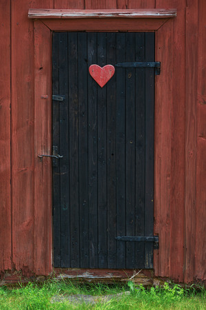 latrine: Traditional vintage restroom or lavatory outside with a heart sign on the black door. Sweden