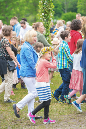 midsummer pole: SINGO, SWEDEN - JUNE 24, 2016: People celebrating midsummer with dance around the maypole. Traditional event in Sweden Editorial