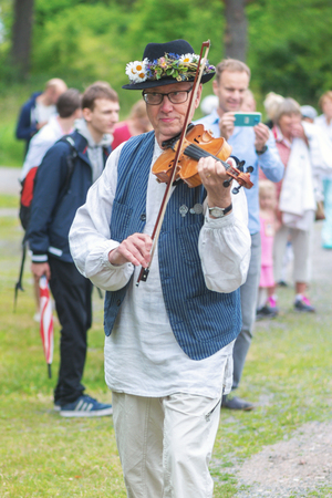 midsummer pole: SINGO, SWEDEN - JUNE 24, 2016: Traditional music is played with violin and accordion for people to dance to. Traditional event in Sweden