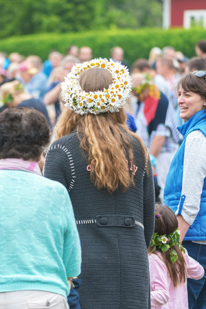SINGO, SWEDEN - JUNE 24, 2016: People celebrating midsummer with dance around the maypole. Traditional event in Sweden Editorial