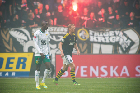ultras: SOLNA, SWEDEN - AUG 28, 2016: Soccer derby between AIK and Hammarby in Allsvenskan at Friends arena. Visibility due to smoke wasnt that good the first half.