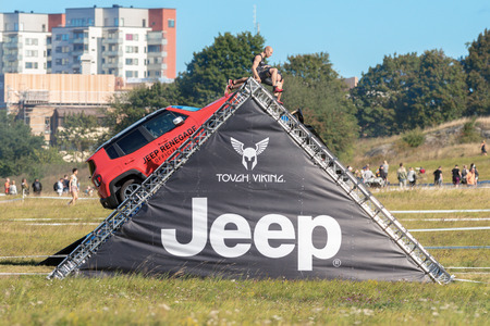 STOCKHOLM, SWEDEN - AUG 27, 2016: Climbing the JEEP obstacle at Tough Viking event at Gardet in Stockholm. Editorial