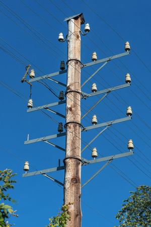 telephone pole: Vintage telephone pole with wiring against a blue sky. Sweden