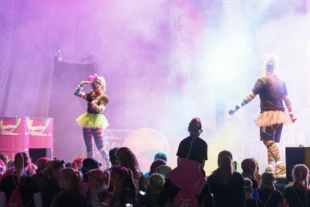 after midnight: STOCKHOLM, SWEDEN - SEPT 18, 2016: Colorful happy people infront of stage at the Color Run Night Edition in Stockholm.