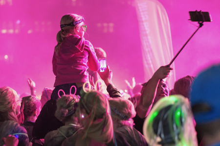 after midnight: STOCKHOLM, SWEDEN - SEPT 18, 2016: Colorful happy kid on fathers shoulders at the Color Run Night Edition in Stockholm.