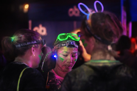 after midnight: STOCKHOLM, SWEDEN - SEPT 18, 2016: Woman in green neon glowing glasses at the Color Run Night Edition in Stockholm. Editorial