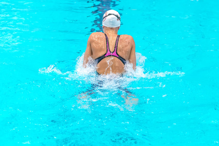 STOCKHOLM, SWEDEN - NOV 5, 2016: Female breaststroke swimmer from the back at the National Swedish swim championships at Eriksdalsbadet.