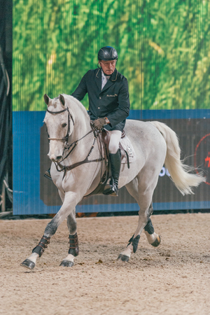 SOLNA, SWEDEN - NOV 27, 2016: John Whitaker at the Friends Christmas Speed Jumping in the Sweden International Horse Show at Friends arena.