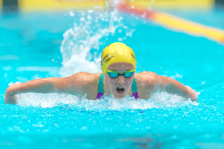 gasping: STOCKHOLM, SWEDEN - NOV 6, 2016: Female Butterfly swimmer at the National Swedish swim competition at Eriksdalsbadet.