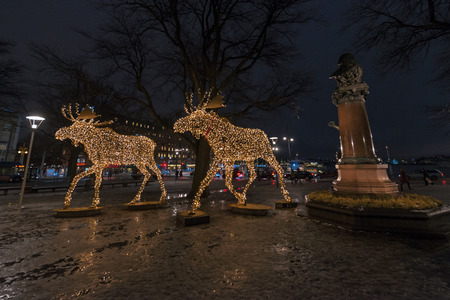 ericsson: STOCKHOLM, SWEDEN - DEC 13, 2016: Group of Christmas moose made of led lights at Nybrokajen with the sculpture of John Ericsson.