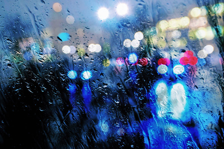 Wet window of defocused colorful lights and reflections from the wet street. Stock Photo