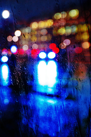 Colorful streetlights thru a wet window during night. Sweden Stock Photo
