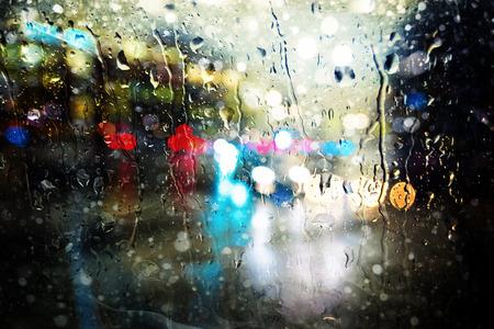Colorful defocused streetlights thru a wet window during night hours.