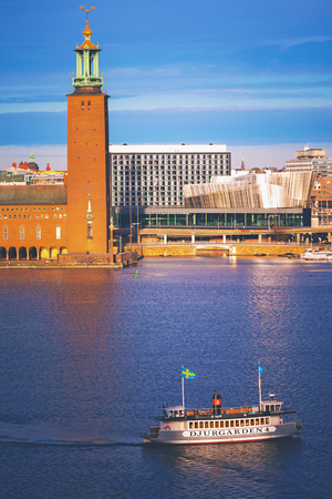 Stockholm City Hall is one of Swedens most famous buildings with a ferry in sunlight