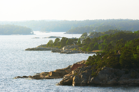 STOCKHOLM, SWEDEN - JUNE 19, 2016: Swedish east coast shoreline in haze with the archipelago of Stockholm. Banco de Imagens