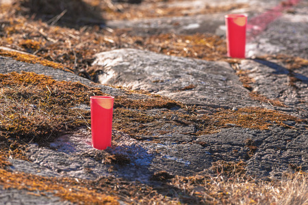 Drilled holes with red pipes to detonate with dynamite and clear the rock for construction. Sweden