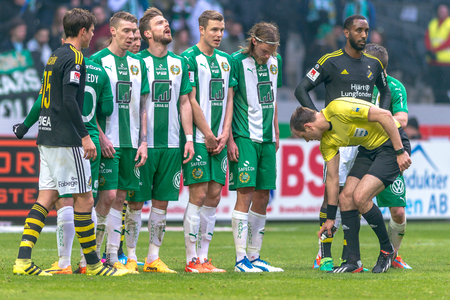 SOLNA, SWEDEN - APRIL 17, 2017: Yellow card and free kick at the derby match between AIK and Hammarby IF at the national stadium Friends Arena in Solna. Hammarby won with 2-1