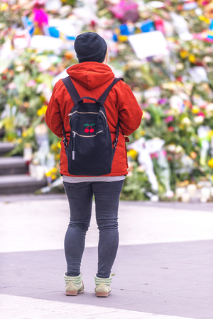 STOCKHOLM, SWEDEN - APRIL 16, 2017: Female mourning in front of the flowerbed at Sergels torg after the terror attack on the 7th of april. Editorial