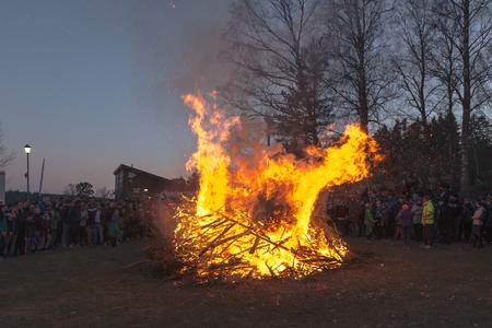ablaze: STOCKHOLM, SWEDEN - APR 30, 2017: Celebration of spring or Valborg at Lida during evening with a flaming big fire.  .