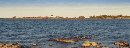 yielding: As daylight ends yielding to evening, lighthouse at panoramic sunset in Sweden with small classic red buildings with stones at the front. Warm light.