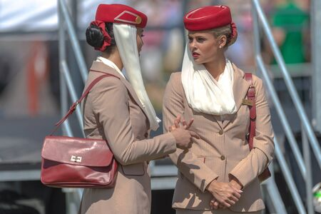 personel: STOCKHOLM, SWEDEN - JUN 6, 2017: Two female airway cabin crew from the sponsor Emirates airways at Nationaldagsgaloppen at Gardet. Editorial