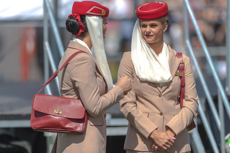 compete: STOCKHOLM, SWEDEN - JUN 6, 2017: Two female airway cabin crew from the sponsor Emirates airways at Nationaldagsgaloppen at Gardet. Editorial