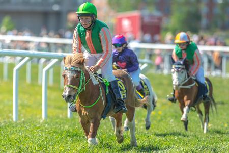 STOCKHOLM, SCHWEDEN - 6. JUNI 2017: Junge Mädchen Jockeys im Ponyrennen bei Nationaldagsgaloppen bei Gardet. Editorial