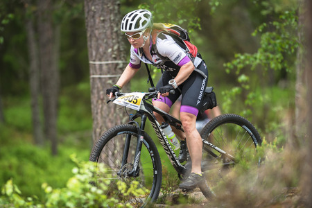 TULLINGE, SWEDEN - JUN 11, 2017: Female MTB rider in the lush forest at Lida Loop in the forests outside of Stockholm.